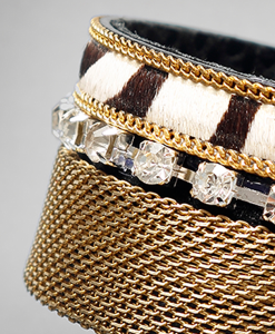 Brazalete de cadena en laton dorado con piel de cebra y tira de strass broche de Omán.
